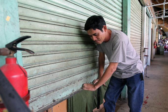 Anh Kính (chủ một cửa hàng trong nhà lồng chợ) đóng cửa sau khi dọn xong hàng hóa