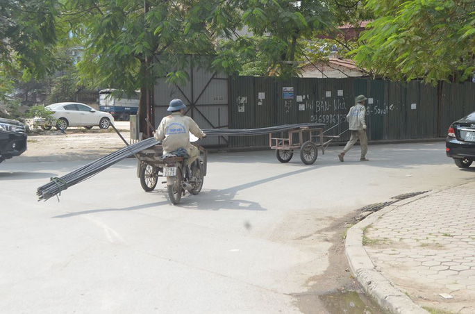 Công nhân dùng xe thô sơ tự chế chở những thanh sắt dài 15-20 m chạy trên đường phố Hà Nội