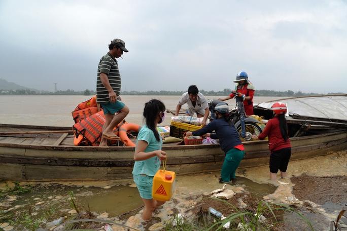 Mực nước lũ dâng cao khiến nhiều nơi bị cô lập kéo dài. Trong ảnh người dân thôn An Phú, xã Tịnh An, TP Quảng Ngãi do bị cô lập nhiều ngày nên đã dùng ghe vận chuyển lương thực, thực phẩm. Ảnh: Tử Trực