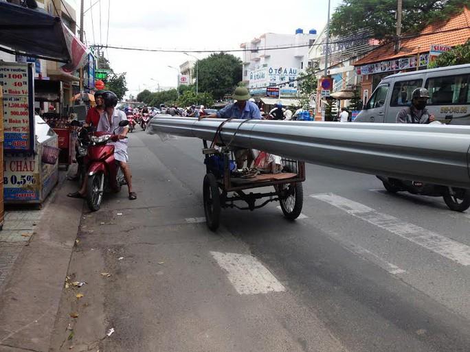 Chiếc xe ba gác chở cuộn tôn dài hơn 10 m di chuyển trên đường Phan Văn Trị (quận Gò Vấp, TP HCM) Ảnh: GIA MINH