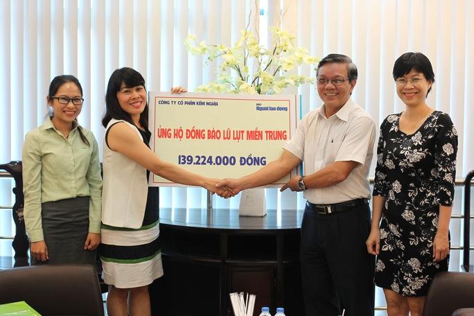 Bà Lê Thị Kiều Hương (thứ 2, từ trái qua) trao tặng gần 140 triệu đồng ủng hộ người dân vùng lũ thông qua Báo Người Lao Động