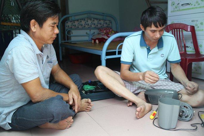 Anh Nguyễn Thành Tâm (trái) thăm hỏi công nhân ở trọ