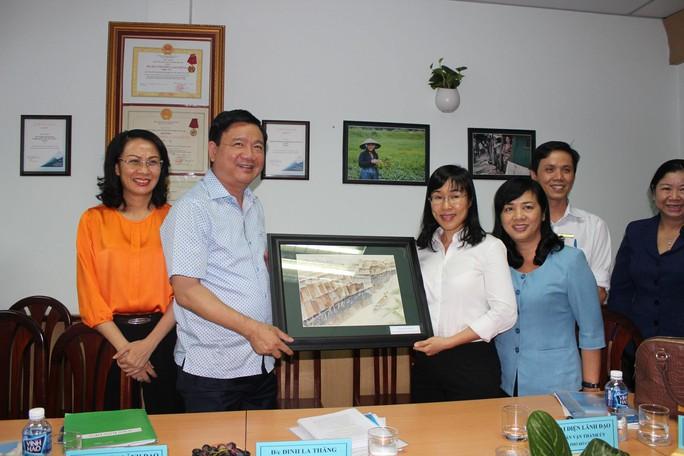 Đại diện Quỹ Trợ vốn CEP (bìa phải) tặng quà lưu niệm cho lãnh đạo Thành ủy và UBND TP HCM