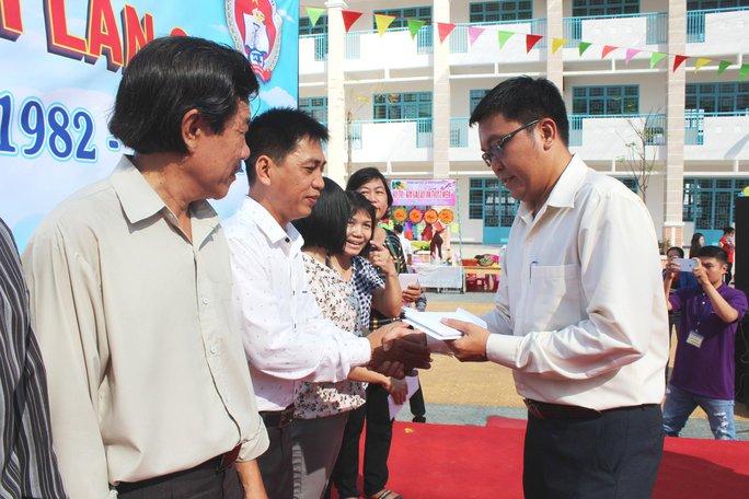 Ông Nguyễn Vũ Hạnh Phúc - Phó Chủ tịch LĐLĐ quận 8, TP HCM - trao tiền hỗ trợ cho giáo viên khó khăn