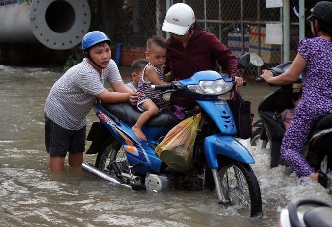 Hai em bé phụ mẹ đẩy xe máy để vượt qua vùng nước ngập.