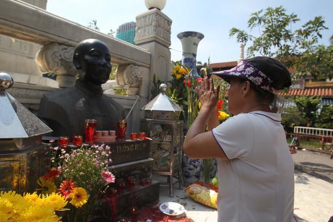 Một tiểu thương thắp hương trước pho tượng Quách Đàm trong khuôn viên chợ Bình Tây để cầu mong việc buôn bán tại chợ tạm diễn ra thuận lợi
