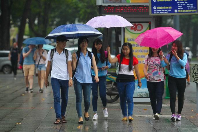 Nhóm khách mang theo mỗi người một chiếc dù, chụp hình trước nhà thờ Đức Bà