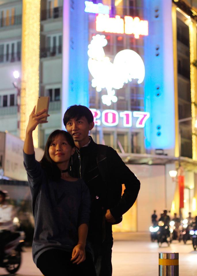 Hai bạn trẻ selfie trước hình ảnh đèn led hình biểu tượng năm Đinh Dậu trên phố đi bộ Nguyễn Huệ