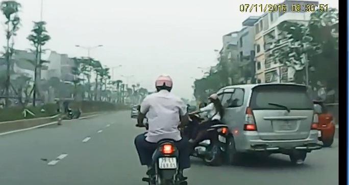 Chiếc xe Toyota Innova lao tới từ bên phải, va chạm xe máy khiến người phụ nữ loạng choạng tay lái rồi ngã xuống đường - Ảnh cắt từ clip