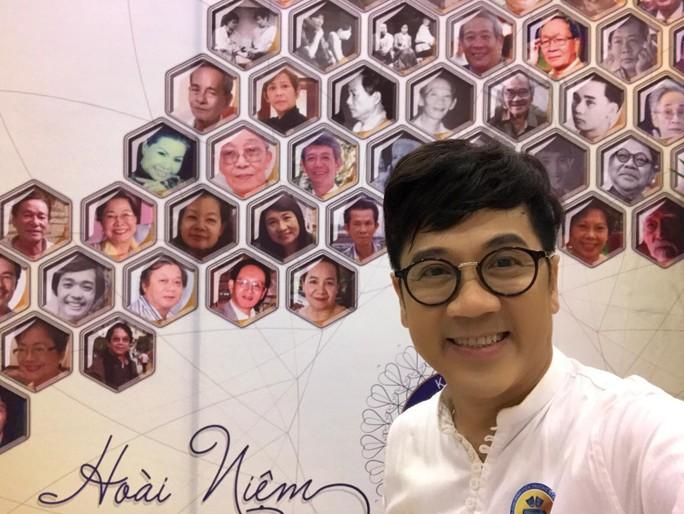 NSƯT Thành Lộc bên cạnh bức tranh là hình ảnh của các thế hệ nhà giáo đã từng dạy tại Trường Nghệ thuật Sân khấu II