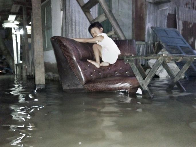 Một em nhỏ phải đu trên ghế để tránh nước khi vui chơi