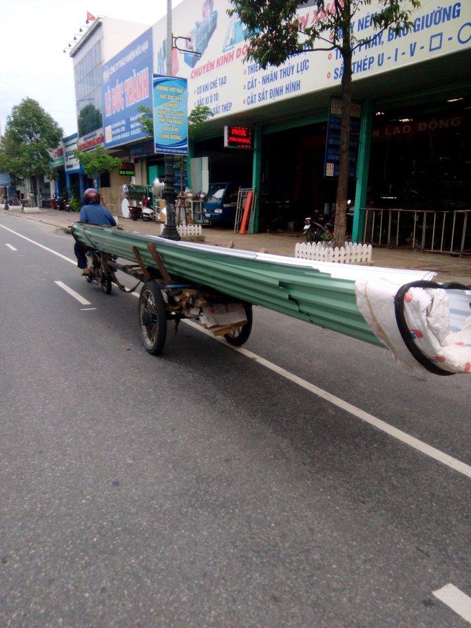 Một chiếc xe bò chở tôn kềnh càng chạy trên đường Điện Biên Phủ
