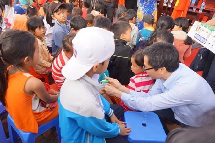 Phó Thủ tướng ân cần phát sữa cho các em học sinh. Ảnh B.N