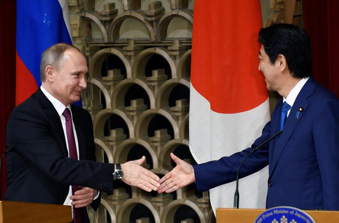 Tổng thống Nga Vladimir Putin (trái) và Thủ tướng Nhật Bản Shinzo Abe bắt tay sau cuộc họp báo chung tại thủ đô Tokyo - Nhật Bản hôm 16-12. Ảnh: REUTERS