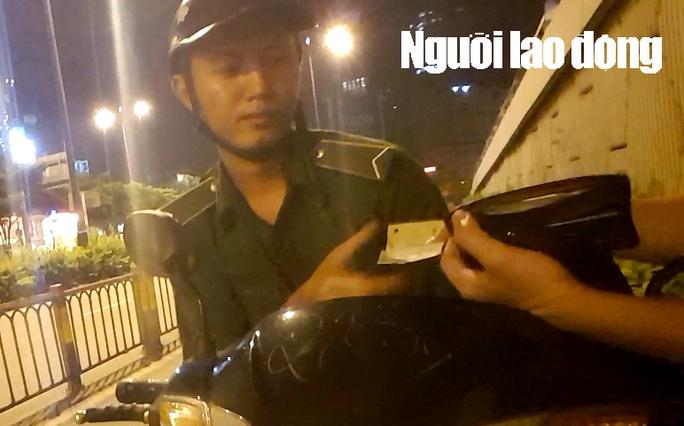 Đối tượng mạo danh TNXP TP HCM, chặn xe người vào hầm Thủ Thiêm trong giờ cấm, thu 100.000 đồng. Ảnh cắt từ video clip.