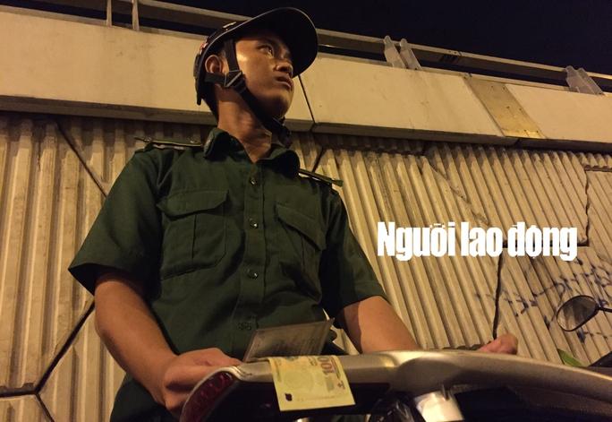 Nam thanh niên mặc sắc phục TNXP TP HCM đang cầm tiền và giấy tờ của người vi phạm. - Ảnh cắt từ clip điều tra.