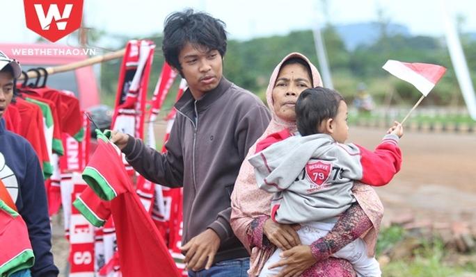 Nhiều gia đình tranh thủ đi từ trong đêm để kịp mang áo, cờ, băng rôn của tuyển Indonesia đến bán cho CĐV