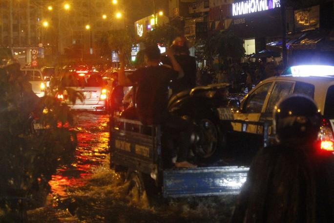 Một số xe ba gác mở dịch vụ đưa xe máy qua các điểm ngập với giá khoảng 100.000 đồng trên đường Nguyễn Hữu Cảnh, khu vực gần cầu Sài Gòn.