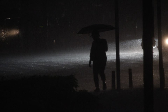 Một người đi bộ chần chừ đứng trên đường Nguyễn Hữu Cảnh, đoạn cầu Thủ Thiêm chờ nước ngập rút bớt mới dám đi tiếp.