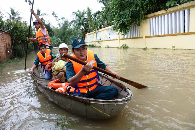 Lực lượng chức năng hỗ trợ người dân có nhà bị ngập ở huyện Tư Nghĩa, tỉnh Quảng Ngãi.Ảnh: Tử Trực