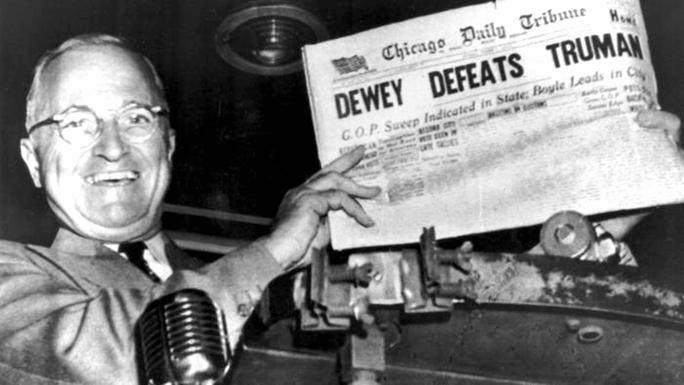 """Tổng thống Harry Truman tươi cười cầm tờ báo Chicago Tribune in dòng tít lớn """"Dewey đánh bại Truman"""" Ảnh: UPI"""