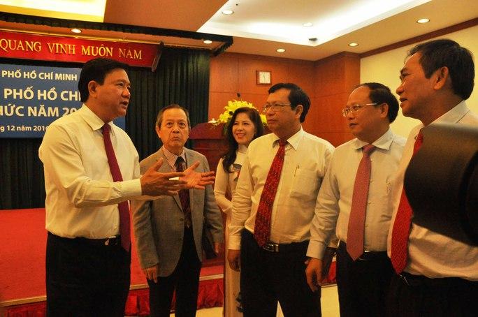 Bí thư Thành ủy TP HCM Đinh La Thăng (bìa trái) và Phó Bí thư Thường trực Thành ủy Tất Thành Cang (thứ 2, từ phải sang) gặp gỡ các trí thức vào ngày 20-12