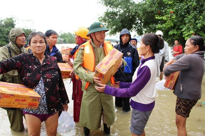 Chủ tịch UBND tỉnh Bình Định Hồ Quốc Dũng trao lương thực cho người dân vùng lũ huyện Tuy Phước