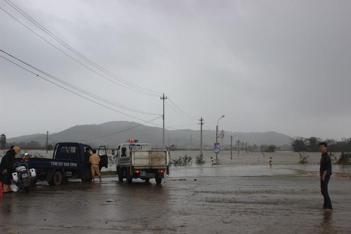 CSGT Công an huyện Tuy Phước lập chốt chặn tại một tuyến đường ngập nước