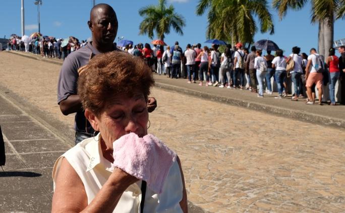 Một người phụ nữ khóc khi ra khỏi đài tưởng niệm. Ảnh: CBC