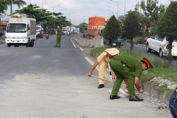 Lực lượng CSGT vừa dọn đá dăm, vừa điều tiết giao thông. Ảnh: C.Linh
