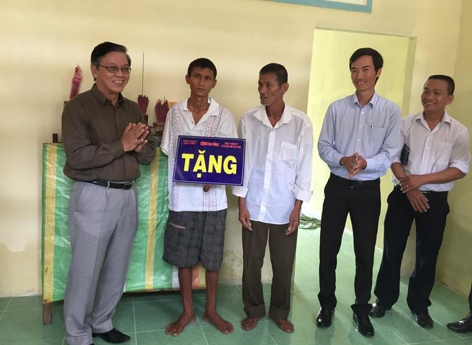 Ông Nguyễn Văn Tín (ngoài cùng bên trái), Phó Tổng Biên tập Báo Người Lao Động bàn giao nhà cho Bé Cụt (thứ 2 từ trái sang)