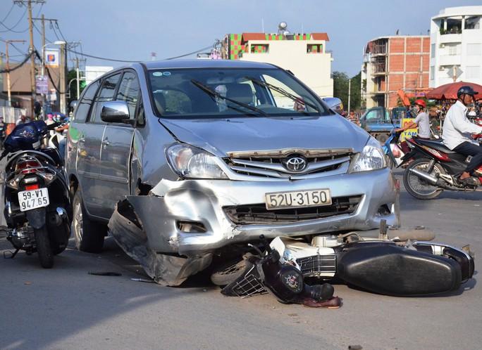 Một chiếc xe máy bị kẹt cứng dưới đầu ô tô trong tình trạng hư hỏng nặng