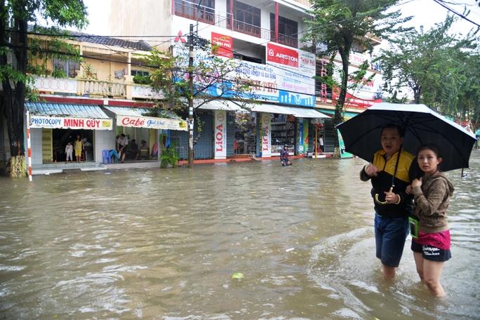 Một đôi nam nữ đang tìm hướng đi cho đỡ ngập nước. Ảnh: Tử Trực
