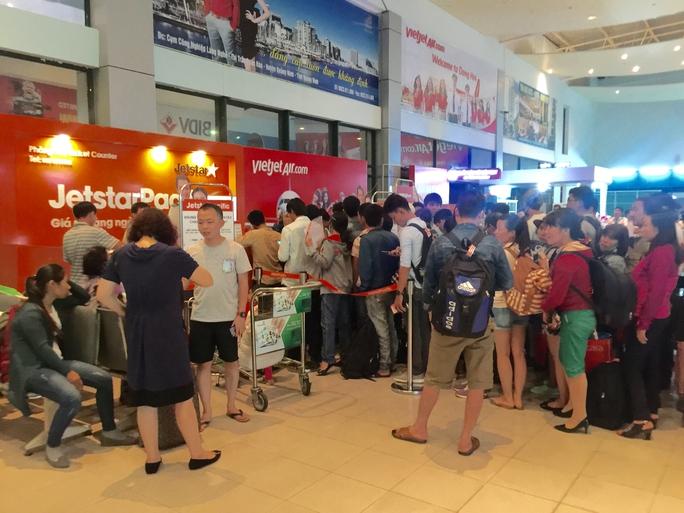 Hành khách tranh thủ làm thủ tục tại sân bay Đồng Hới do một chuyến bay bị hoãn hôm 26-9. Ảnh: DUY CƯỜNG