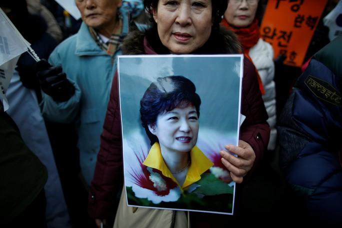 Một người ủng hộ cầm ảnh của Tổng thống Hàn Quốc Park Geun-hye trong cuộc biểu tình ở Seoul hôm 17-12. Ảnh: REUTERS