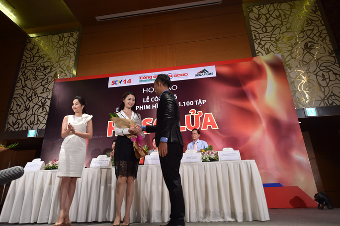 Đại diện nhà sản xuất tặng hoa cho đại diện ê-kíp thực hiện phim tại buổi công bố dự án. Ảnh: Nguyễn Hữu Phước