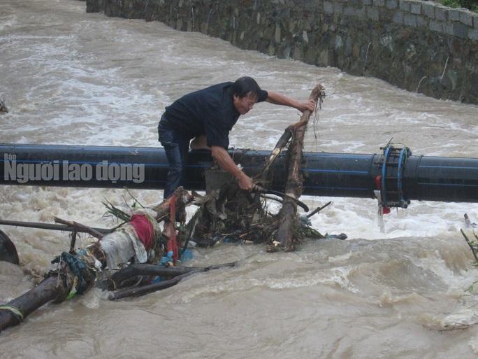 Người dân liều mình cứu hệ thống nước máy khỏi bị nước cuốn trôi