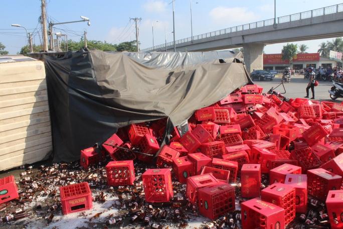 Xe lật, hàng trăm két bia đổ ra đường vùi 2 người đi xe máy ở phía sau