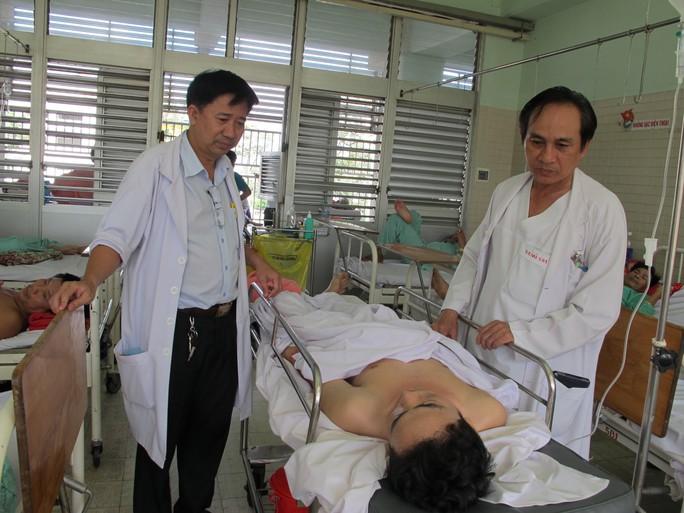 Bác sĩ Vũ (phải) và bác sĩ Trí thăm hỏi bệnh nhân sau ca phẫu thuật