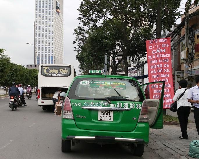Một chiếc xe khách xếp dỡ hàng ngay dưới bảng thông báo kế hoạch cấm xe dừng, đậu