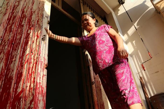 Sơn đỏ bám kín cửa sắt và mùi hôi nồng nặc tại nhà bà H. trên đường Phong Phú (quận 8).