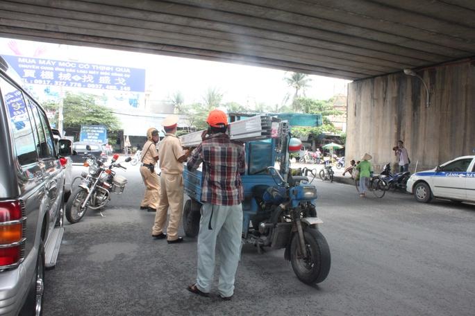 Các chiến sĩ CSGT Bình Triệu đang giúp chủ phương tiện xuống hàng tại chỗ vì chở quá quy định cho phép