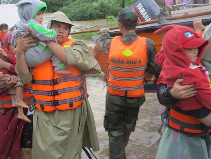 Lực lượng cứu hộ đưa dân vùng lũ đến nơi an toàn - ảnh: Tiến Sĩ