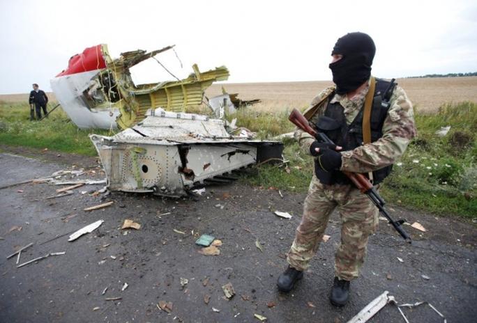 Một phiến quân thân Nga đứng tại hiện trường vụ rơi MH17 ở làng Hrabove, miền Đông Ukraine năm 2014. Ảnh: Reuters