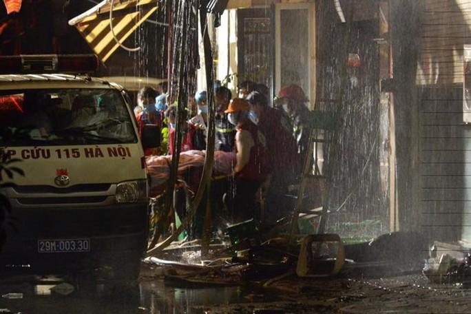 Một nạn nhân tử vong trong vụ cháy quán karaoke được đưa ra ngoài - Ảnh: CAND