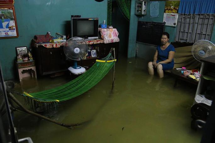 Bà Nguyễn Thị Tám, ngồi thẫn thờ trong ngôi nhà ngập nước tại phường An Phú, quận 2. Bà Tám cho biết bà đã nhiều lần nâng nền nhưng ngập vẫn hoàn ngập