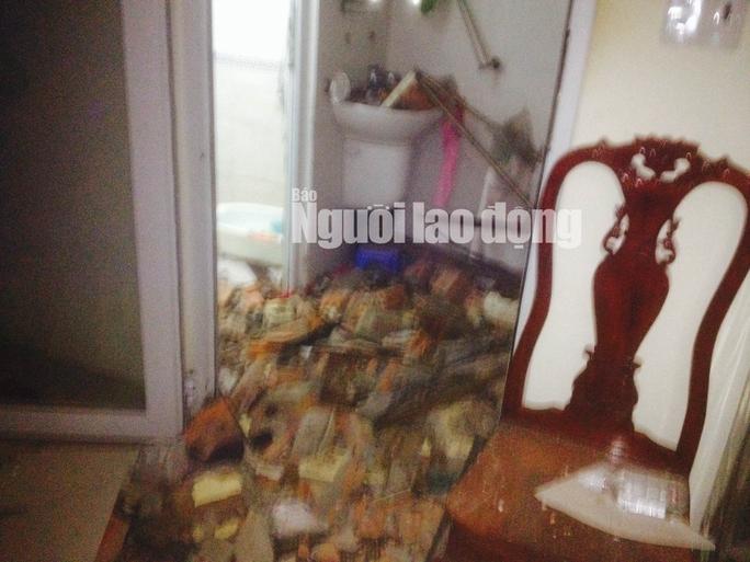 Một bức tường nhà dân gần đó bị vỡ vụn