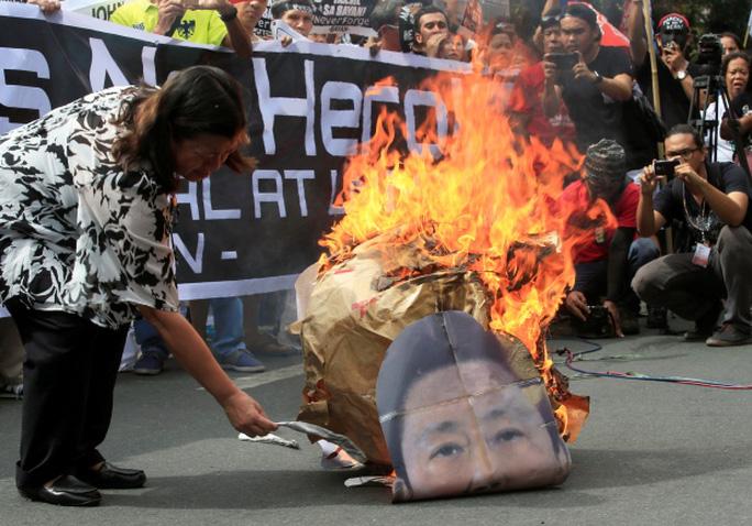 Một người biểu tình đốt hình ông Marcos. Ảnh: Reuters