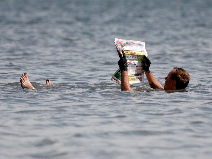 Người đàn ông đọc báo giữa hồ nước mặn Tus ở vùng Khakassia vủa Nga. Ảnh: Reuters