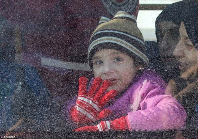 Em bé trên chiếc xe buýt rời khỏi Aleppo. Ảnh: Reuters